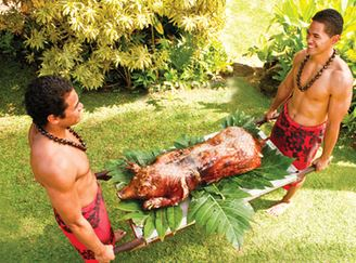 a photo of two polynesian villagers presenting an imu roast pig for dinner at the Alii Luau at the Polynesian Cultural Center.