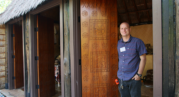 Photo of David Duffin, Facilities Planning Manager at the Polynesian Cultural Center shows the beautiful machine milled wood doors in the Fijian Village courtesy of Mike Foley