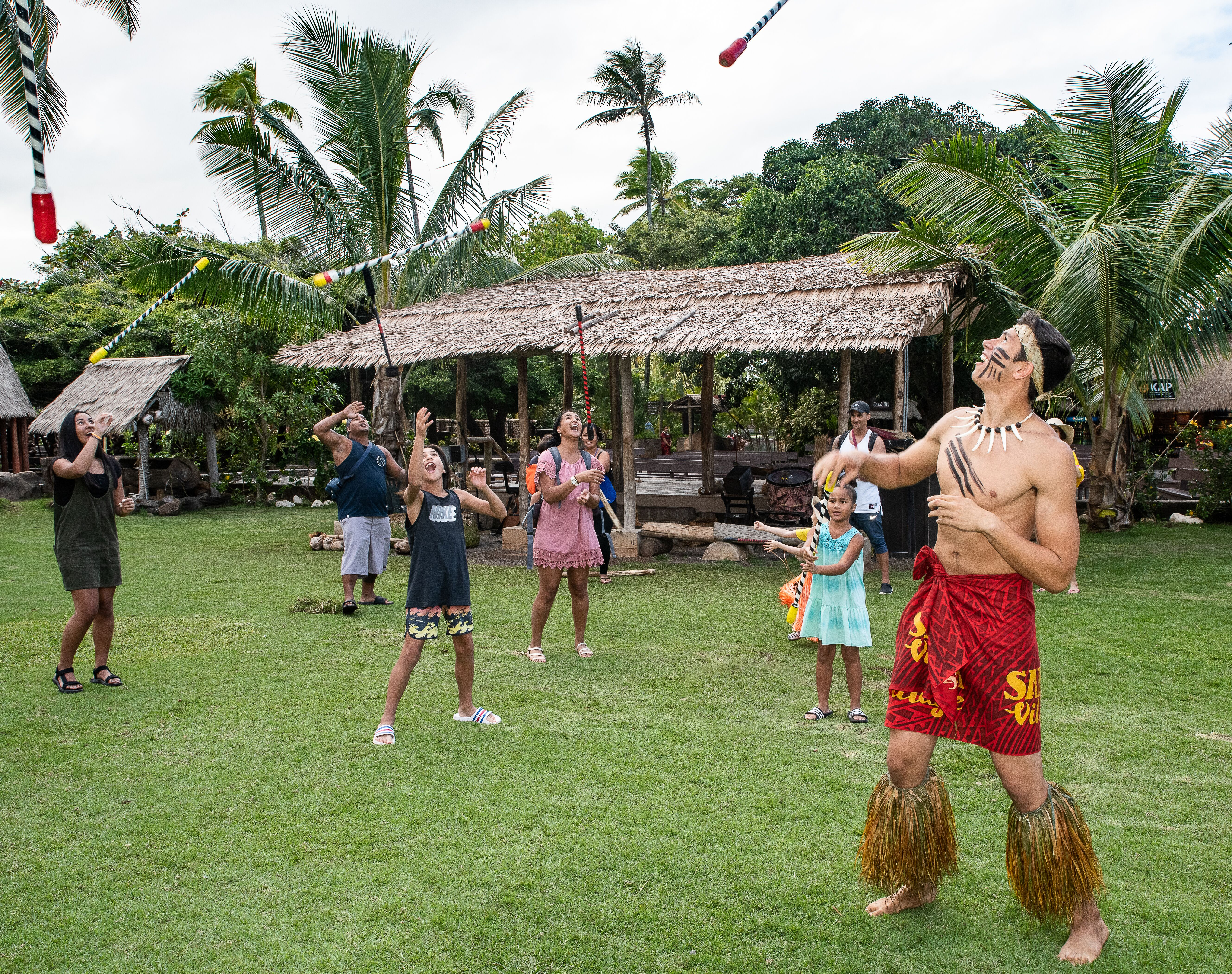 photo of guests and Samoan villager tossing 'fireknives'