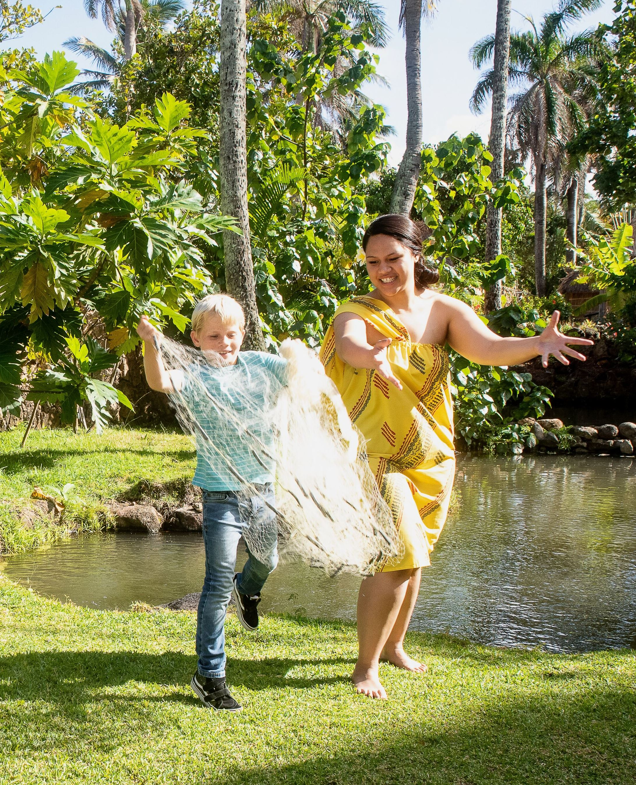 Picture of boy tossing a fishing net in the Hawaiian Village at the Polynesian Cultural Center