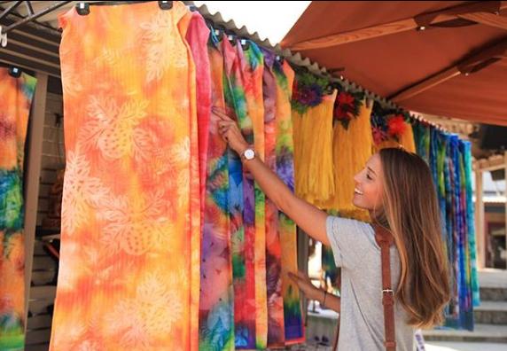 A woman shopping for Tahitian Pareos at the Hukilau Marketplace