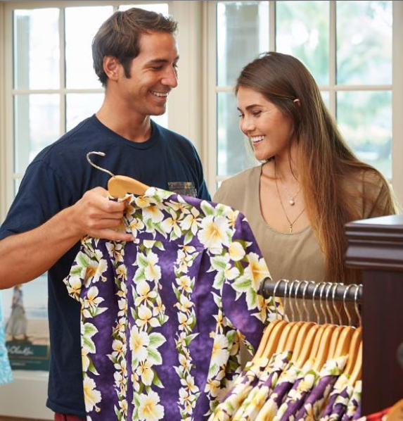 Two people shopping for aloha shirts at Nona's Tropical Threads