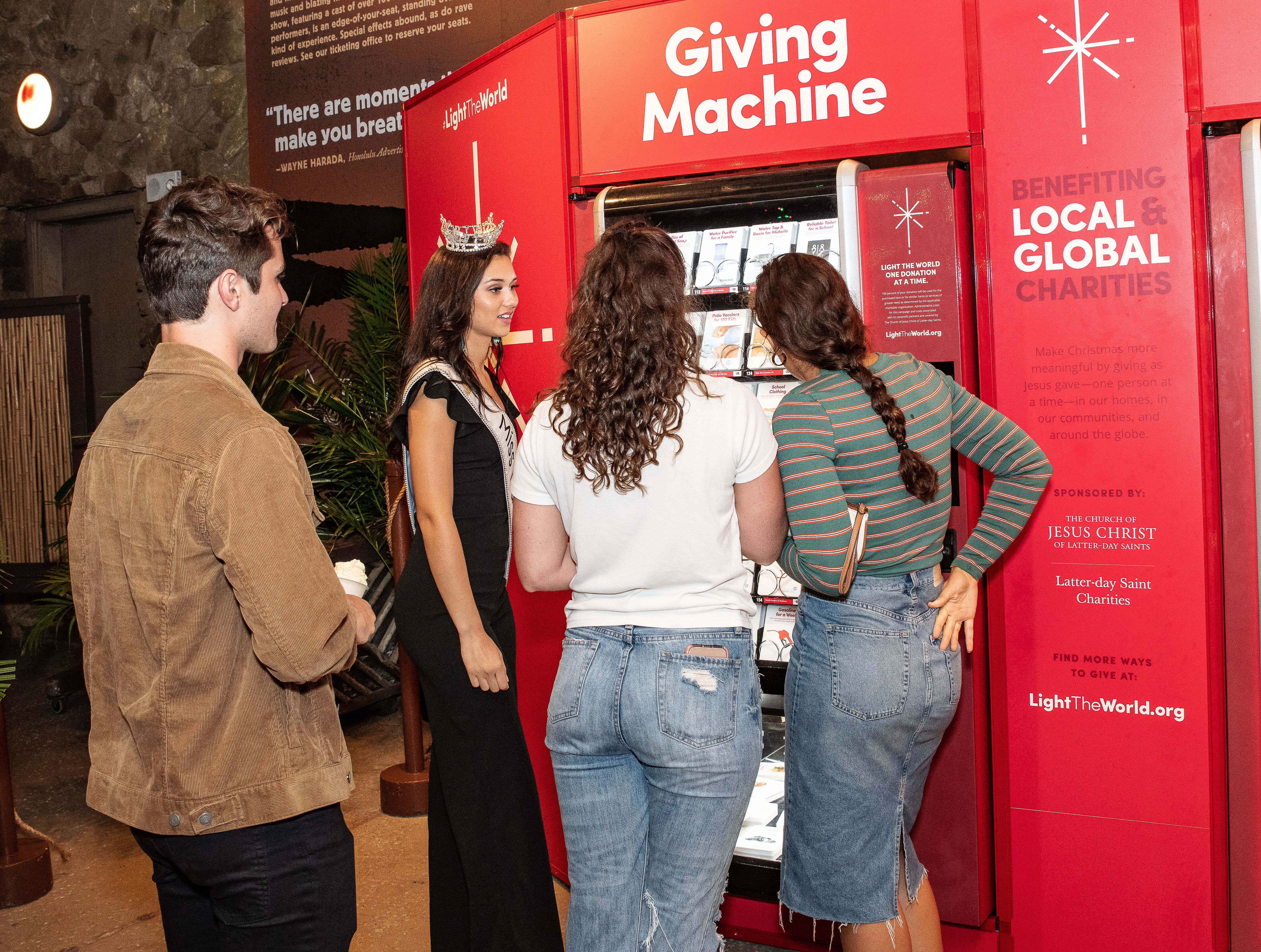 Photo of Miss Hawaii, Nikki Holbrook, helping 3 visitors to place their donation order at the Giving Machine