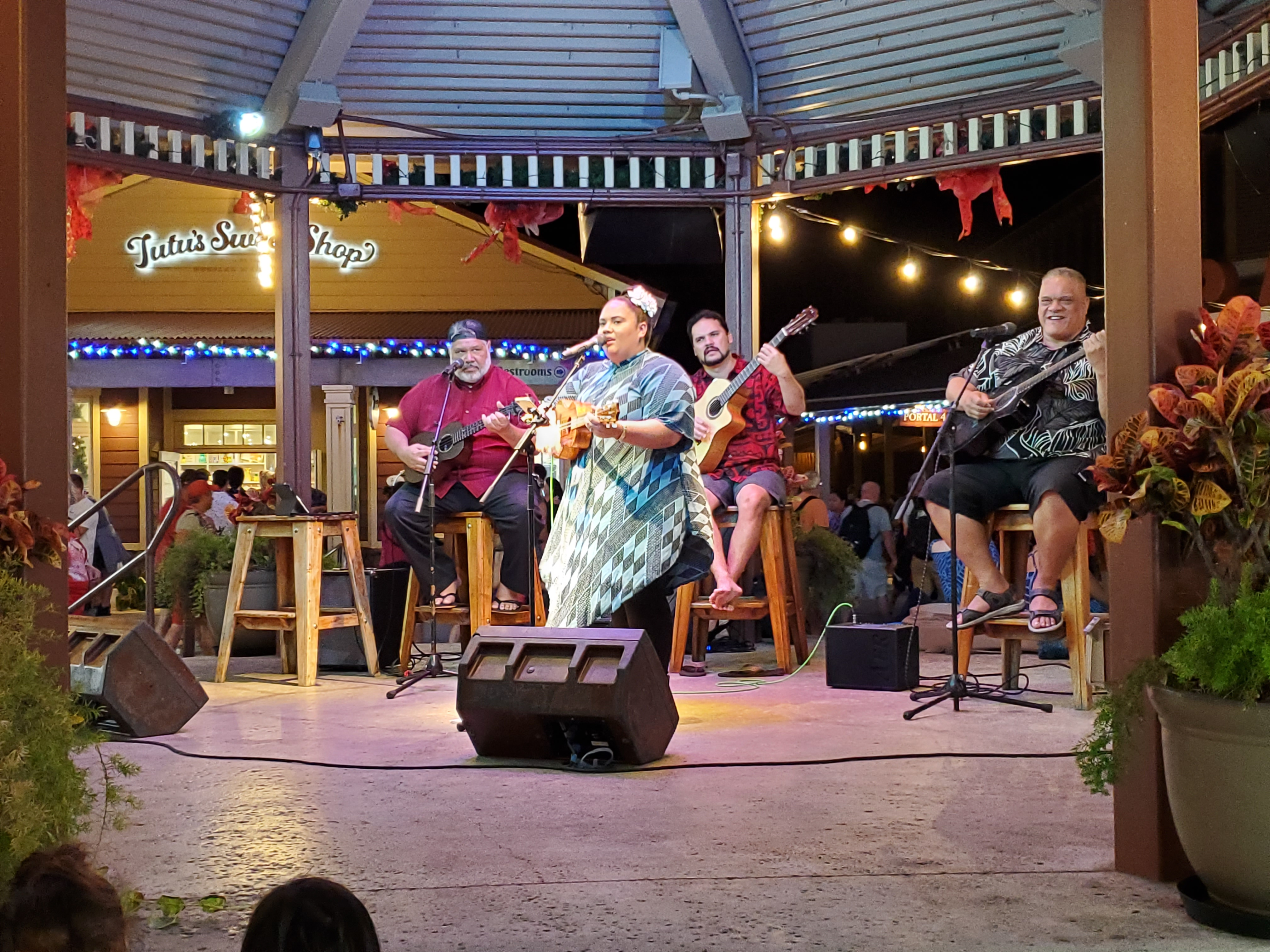 Photo showcasing entertainment from the gazebo in the Hukilau Marketplace's center Gazebo, featuring (insert name of musicians)