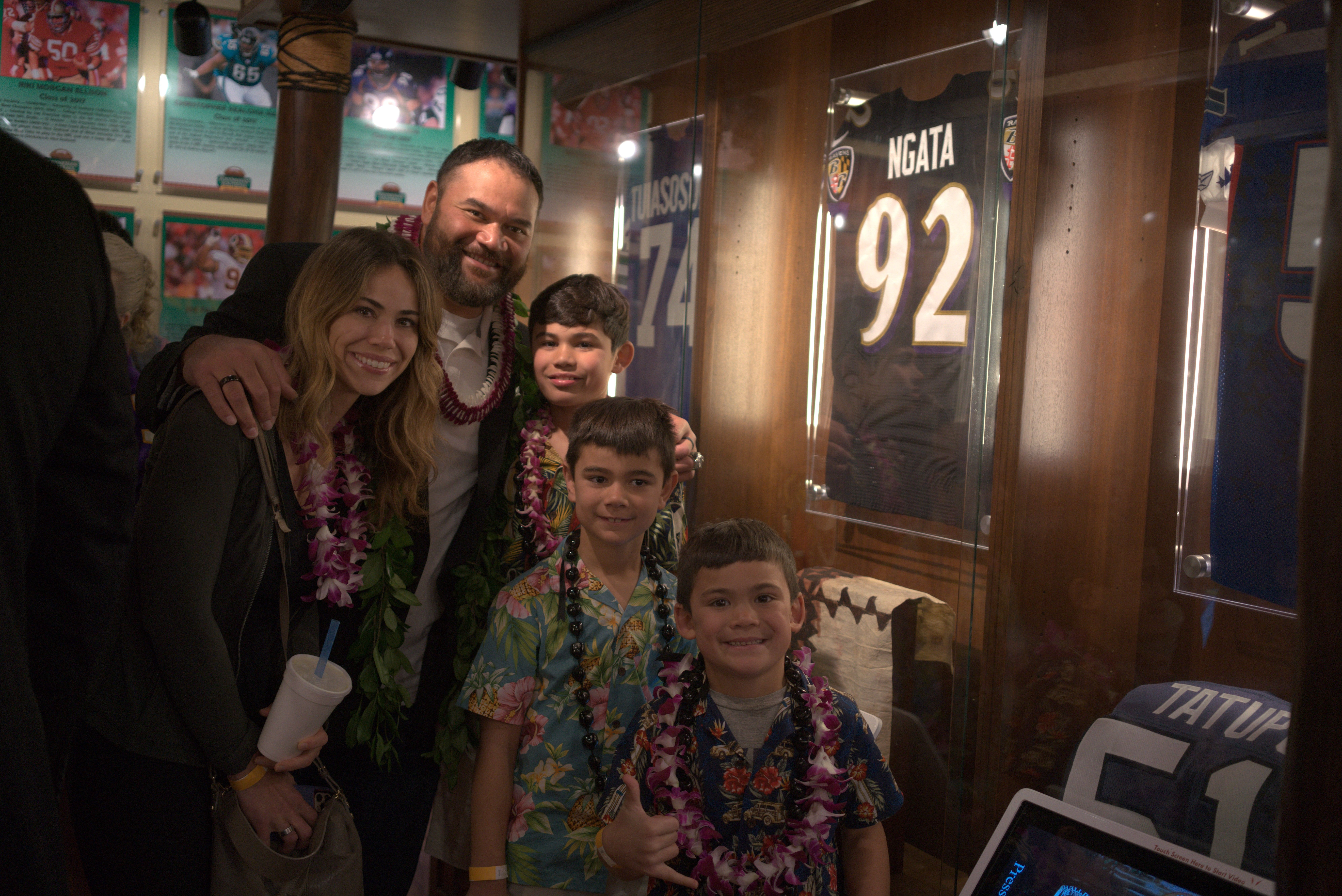 Photo of Haloti Ngata and his family stand next to his display case at the Polynesian Football Hall of Fame at the Polynesian Cultural Center during the induction ceremony festivities.