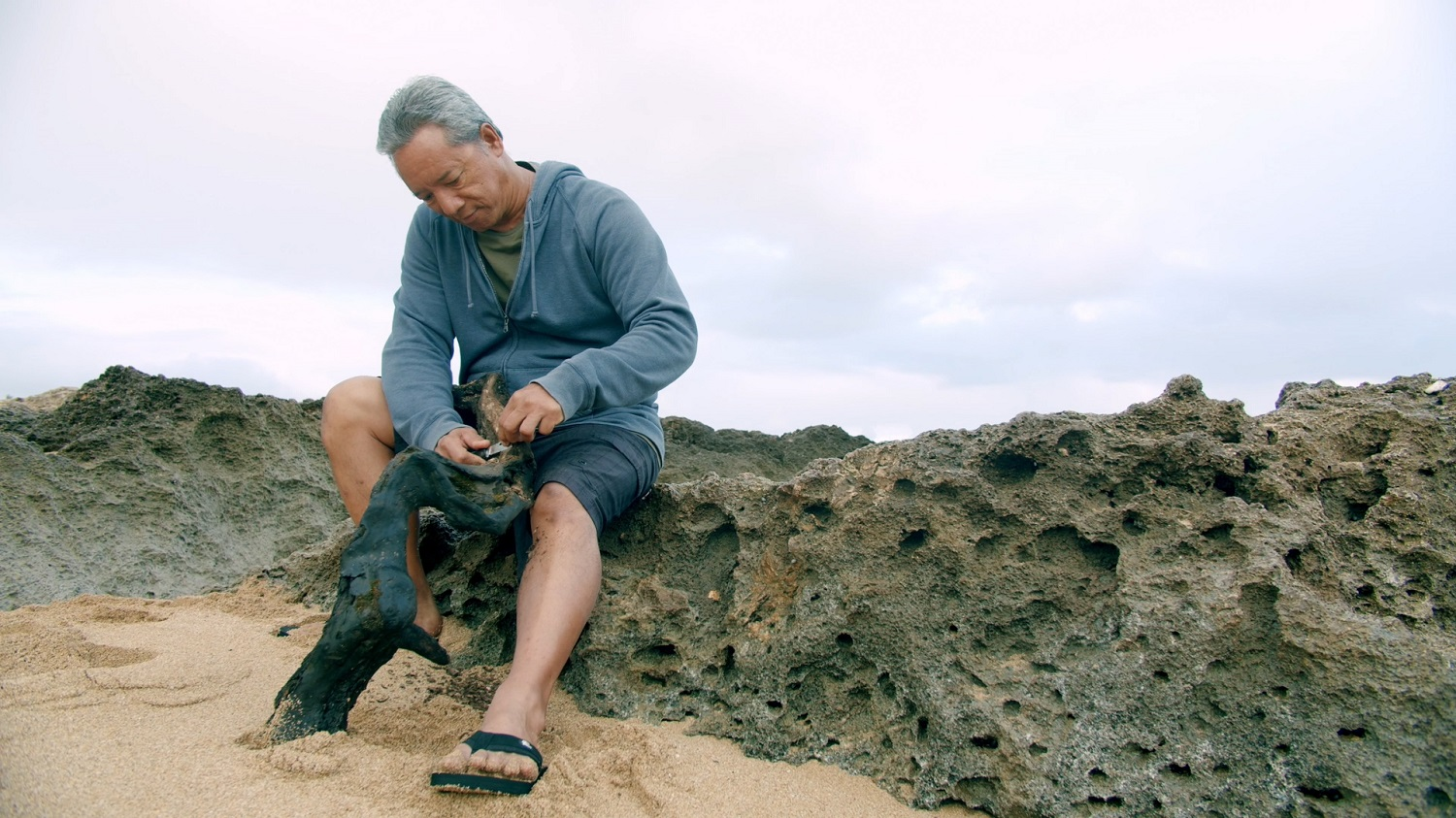 Photo of Kawika Eskaran as he works with a branch by the sea