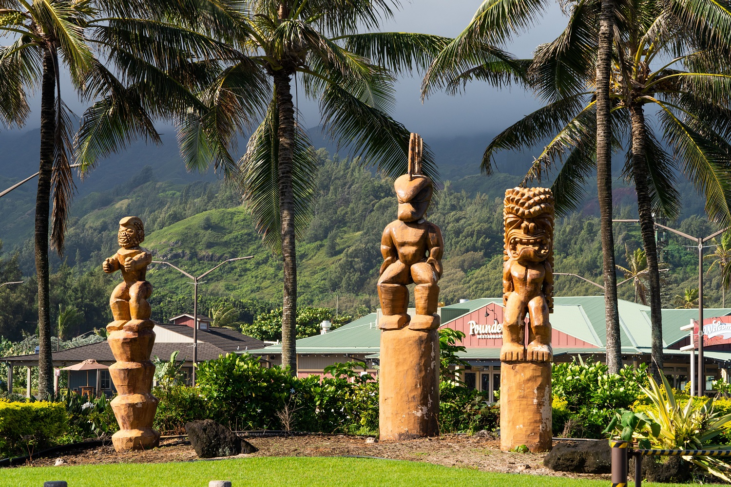 Photo of three giant tikis that are placed just outside the main entrance to the Polynesian Cultural Center