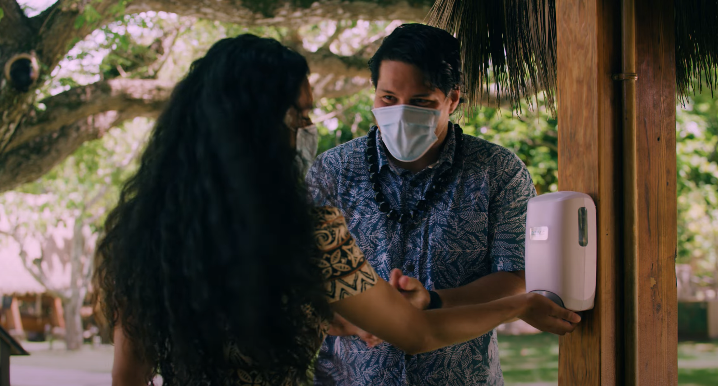 Two people at the Polynesian Cultural Center utilizes on of the hand sanitizing stations. The Center plans to fully reopen in March, 2021.
