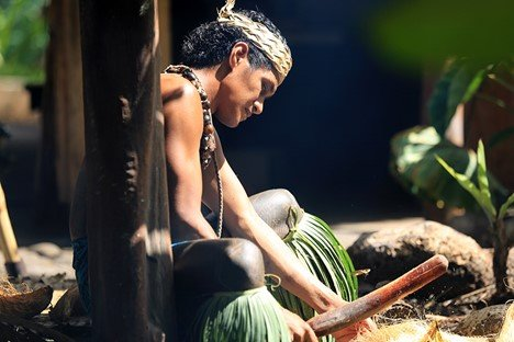 Samoan man starting fire with two hibiscus sticks and coconut husks at the Polynesian Cultural Center - Exclusive ticketing available January and February 2021.
