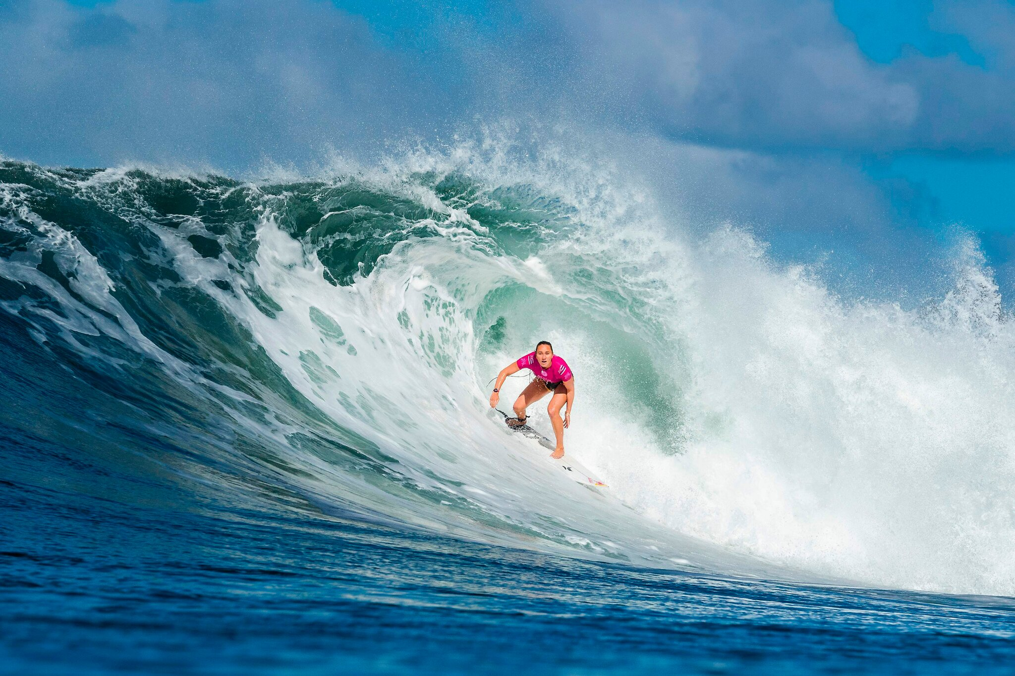 image of female surfer Carissa Moore catching a wave from her professional website
